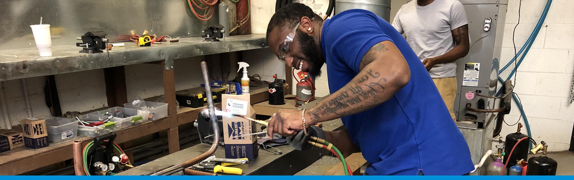 Man Welding Piping for HVAC Program